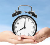 Holding alarm clock in hands — Stockfoto
