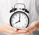 Holding alarm clock in hands — Stock Photo