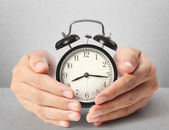 Man holding alarm clock in hands — Stock Photo