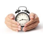 Man holding alarm clock in hands — Stock Photo