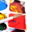 Artists palette with various colour paints and brush — Stock Photo #40410909