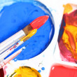Artists palette with various colour paints and brush — Stock Photo
