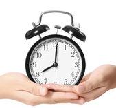 Holding alarm clock in hands — Stock Photo