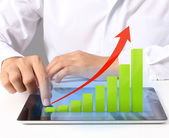 Tablet screen with graph and  hand  — Stock Photo