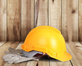 Yellow hardhat and old leather gloves  — Stock Photo