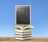 Blackboard on book  with wooden frame  — Stockfoto
