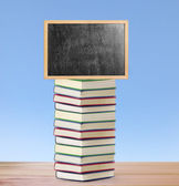 Blackboard on book  with wooden frame  — Stock Photo