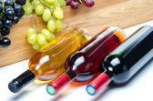 Bottles of wine in front of a wooden box with grapes — Stock Photo