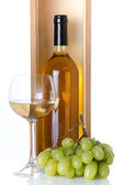 Bottles of wine in a wooden box with a glass of wine and white g — Stockfoto