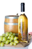 Bottle of wine with white grapes and a cask on a burlap bag — Photo