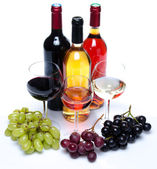 Bootles and glasses of wine with black, red and white grapes — Stock Photo