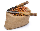 Hazelnuts in a burlap bag with a nutcracker — Stock Photo