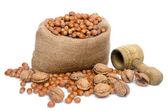 Hazelnuts in a burlap bag with a nutcracker — Stock Photo