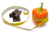 Measuring tape around a pepper and chocolate — Stock Photo
