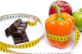 Measuring tape around a pepper and chocolate with apples — Stock Photo