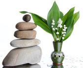Composition of stacked pebbles with a vase of lilies — Stock Photo