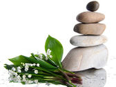 Composition of stacked pebbles with a bouquet of lilies — Stock Photo