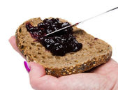 Woman's hand putting blackberry jam on a toast — Stock Photo