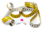 Measuring tape with pills — Stock Photo