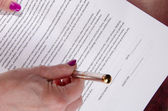 Woman's hand giving a pen for sign a paper — 图库照片