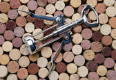 Background of wine corks with a cork screw — Stock Photo