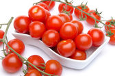 Tomatoes in a white cut and cherry tomatoes — Stock Photo