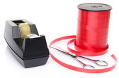 Roll of shiny red ribbon gift with scissors and scotch tape — Stock Photo