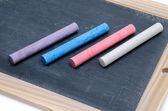 Slate with chalk sticks — Stock Photo