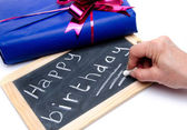 Happy birthday written on a slate blackboard with a gift — Photo