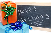 Happy birthday written on a slate blackboard with gifts — Stock Photo