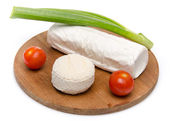 Composition of goat cheese on a wooden cutting board — Stock Photo