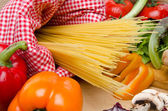 Composition of uncooked spaghetti surrounded by vegetables — Foto de Stock