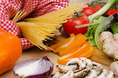 Composition of uncooked spaghetti surrounded by vegetables — Stock Photo