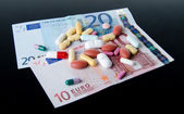 Pills, tablets and capsules spread on banknotes — Stock Photo