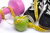 Pink dumbell, an apple and fitness shoes with a tape measure — Stock Photo