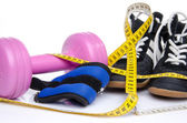 Pink dumbell, ankle weights and fitness shoes with a tape measur — Stock Photo