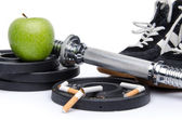 Dumbells, fitness shoes with an apple and broken cigarettes — Stock Photo
