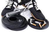 Dumbells, fitness shoes with broken cigarettes — Stock Photo