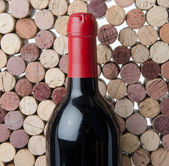 Bottle of wine on a background of corks — Stock Photo