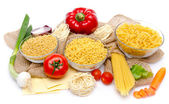 Different types of uncooked pasta and vegetables on a burlap — Stock Photo