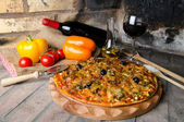 Pizza with wine and some ingredients on a firebricks background — Stock Photo