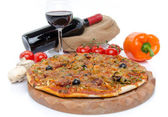 Composition with a pizza, some vegetables, a glass and a bottle  — Stock Photo