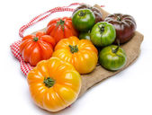 Green, yellow, orange and purple tomatoes on a burlap — Stock Photo