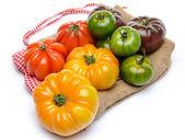 Green, yellow, orange and purple tomatoes on a burlap — Stockfoto