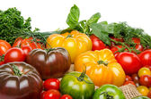 Composition of different varieties of tomatoes and herbs on a bu — Stockfoto