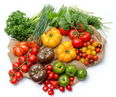 Composition of different varieties of tomatoes and herbs on a bu — Stock Photo