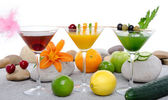 Composition with a orange, cherry and green vegetables cocktails — Stock Photo