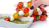Hand dipping a skewer of cherry tomatoes and mozzarella in a vin — Stock Photo