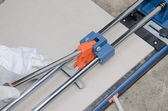 Tiler using a tile cutter — Stockfoto