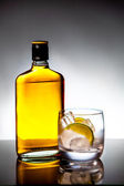 Glass and bottle of hard liquor — Stock Photo